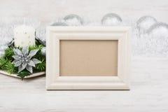 Decoración de la Navidad con la vela y marco vacío de la foto en el fondo de madera blanco Maqueta blanca del marco Fotografía de archivo libre de regalías