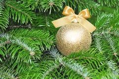 Decoración de la Navidad de la forma de la bola del oro en árbol con el arco Imagen de archivo libre de regalías