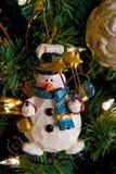 Decoración de la Navidad del muñeco de nieve en un árbol Fotografía de archivo