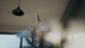 Decoración de la Navidad del oro, ornamento de una estrella brillante en el árbol de navidad del ` s del Año Nuevo metrajes