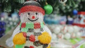 Decoración de la Navidad - el muñeco de nieve centellea debajo del árbol de navidad almacen de video