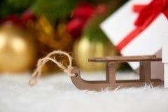 Decoración de la Navidad en el primer de la rama de árbol de abeto, el juguete de madera del trineo, los regalos, la bola de Navi Fotos de archivo libres de regalías