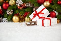 Decoración de la Navidad en el primer de la rama de árbol de abeto, el juguete de madera del trineo, los regalos, la bola de Navi Imagen de archivo libre de regalías