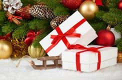 Decoración de la Navidad en el primer de la rama de árbol de abeto, el juguete de madera del trineo, los regalos, la bola de Navi Foto de archivo libre de regalías