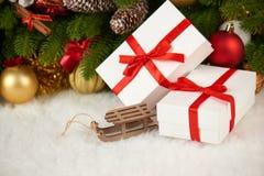 Decoración de la Navidad en el primer de la rama de árbol de abeto, el juguete de madera del trineo, los regalos, la bola de Navi Imagenes de archivo