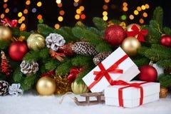 Decoración de la Navidad en el primer de la rama de árbol de abeto, el juguete de madera del trineo, los regalos, la bola de Navi Fotografía de archivo libre de regalías