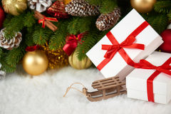 Decoración de la Navidad en el primer de la rama de árbol de abeto, el juguete de madera del trineo, los regalos, la bola de Navi Imagen de archivo