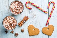 Decoración de la Navidad en fondo de madera con las galletas en corazón de la forma, bastón y dos vidrios de cacao Foto de archivo libre de regalías