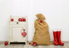 Decoración de la Navidad en los colores rojos y blancos con el saco, presentes imagen de archivo libre de regalías