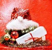 Decoración de la Navidad, fondo rojo con la nieve para los saludos de la postal, diseño del juguete en los regalos macros de Navi Fotos de archivo libres de regalías