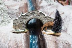 Decoración de la decoración de la Navidad la gran de los ciervos del yeso bebe el agua de la raza del río en invierno en la nieve Foto de archivo libre de regalías