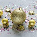 Decoración de la Navidad Juguetes de oro de la Navidad y estrellas coloridas en fondo concreto imagen de archivo libre de regalías