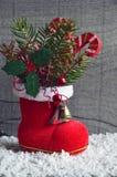 Decoración de la Navidad La bota roja del ` s de Papá Noel con la rama de árbol de abeto, baya decorativa del acebo se va, bastón Fotos de archivo libres de regalías