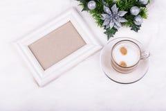 Decoración de la Navidad, marco vacío de la foto y café del latte en el fondo blanco Maqueta blanca del marco Imagen de archivo