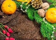 Decoración de la Navidad, puntilla de conos spruce, mandarinas y nueces en marco del Año Nuevo de la arpillera Fotografía de archivo libre de regalías