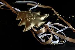 Decoración de la Navidad que representa un árbol de oro con el cordón coloreado en fondo negro fotografía de archivo libre de regalías