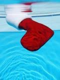 Decoración de la Navidad que se hunde abajo en el agua de una piscina Imagen de archivo