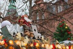 Decoración de la Navidad: Santa Claus que se sienta en el tejado adornado con la guirnalda y el árbol de abeto Mercado de Navidad Imagen de archivo libre de regalías
