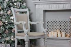 Decoración de la Navidad - sitio con la silla, la chimenea y el árbol de navidad hermosos Foto de archivo libre de regalías