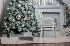 Decoración de la Navidad - sitio con la silla, la chimenea y el árbol de navidad hermosos Fotos de archivo
