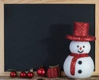 Decoración de la pizarra de la Navidad con el muñeco de nieve y la caja de regalo roja Foto de archivo libre de regalías
