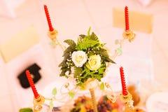 Decoración de la tabla con las flores y las velas rojas Imágenes de archivo libres de regalías