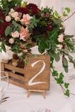 Decoración de la tabla de la boda con las flores rojas y rosadas y la caja de madera Imagenes de archivo