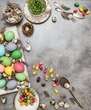Decoración de la tabla de Pascua con los huevos y los dulces coloreados Fotografía de archivo