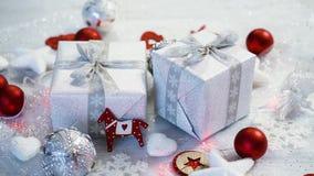 Decoración de la tabla de la Navidad con los presentes de plata y las chucherías rojas metrajes