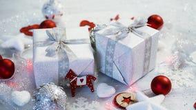 Decoración de la tabla de la Navidad con los presentes de plata y las chucherías rojas almacen de video