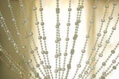 Decoración de las perlas de las cortinas y fondo retroiluminado fotos de archivo