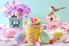 Decoración de los colores en colores pastel de Pascua con los huevos de caramelo en pequeño cubo Fotografía de archivo libre de regalías