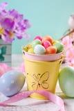 Decoración de los colores en colores pastel de Pascua con los huevos de caramelo en pequeño cubo Imágenes de archivo libres de regalías