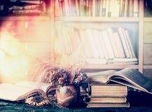 Decoración de los libros viejos y de las flores del otoño en taza en la biblioteca Imágenes de archivo libres de regalías