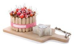 Decoración de madera de la Navidad con los dulces y una vela en un fondo blanco Foto de archivo