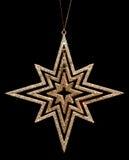 Decoración de oro de la estrella de la Navidad del brillo en negro imagen de archivo