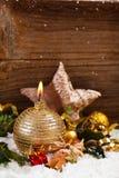 Decoración de oro de la vela y de la Navidad en nieve Imagen de archivo libre de regalías