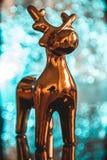 Decoración de oro de la Navidad del reno encima de una tabla Imagenes de archivo