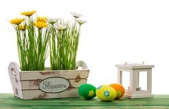 Decoración de Pascua - caja con las flores, los huevos y la linterna en fondo de madera Fotos de archivo
