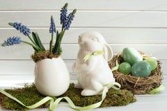 Decoración de Pascua con el conejo, las flores de la primavera y los huevos blancos Conejito del este Imágenes de archivo libres de regalías