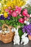 Decoración de Pascua con las flores, los huevos, los conejitos y la torta Fotos de archivo libres de regalías
