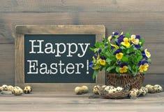 Decoración de Pascua con los huevos de codornices, las flores del pensamiento y bla del vintage Imagen de archivo