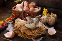 Decoración de Pascua de la gallina en la jerarquía y de la cesta de mimbre con los huevos Fotografía de archivo