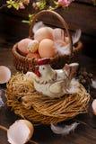 Decoración de Pascua de la gallina en la jerarquía y de la cesta de mimbre con los huevos Fotografía de archivo libre de regalías