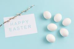 Decoración de Pascua, huevos blancos y ramita del sauce en vagos azules claros Imagen de archivo