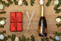 Decoración de Pascua, presente, bootle del champagner y vidrios del champán en la madera Foto de archivo libre de regalías