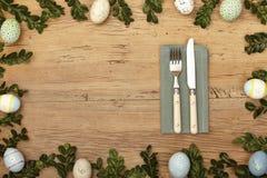 Decoración de Pascua, servilleta, knive y bifurcación en la madera Imágenes de archivo libres de regalías