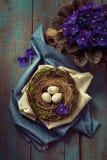 Decoración de Pascua - una jerarquía con los huevos de madera y las flores violetas Imagen de archivo libre de regalías