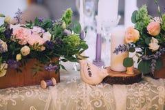 Decoración de una tabla de la boda con una composición de flores en potes de madera, un pájaro de cerámica, velas y una rebanada  Imagen de archivo libre de regalías