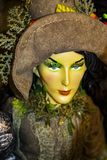 Decoración de Witchy Halloween - detalle de la bruja hermosa de la tierra en traje y sombrero marrones con los ojos muy verdes -  foto de archivo libre de regalías